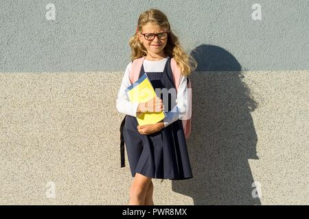 Outdoor portrait of girl elementary school pupil, wearing glasses, with backpack, books and notebooks, background gray wall - Stock Photo