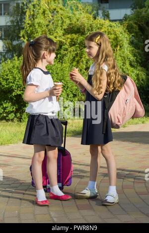 Rear view of two schoolgirl girlfriends with backpacks eating ice cream. - Stock Photo