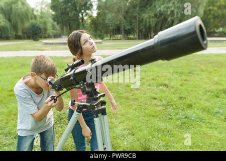 Children teenagers in the park looking through a telescope. - Stock Photo