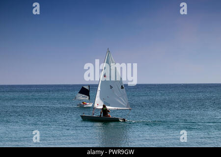 Two small sailboats with one man crew sail the Aegean sea near the shores of Santorini, Greece on a hot summer day. - Stock Photo