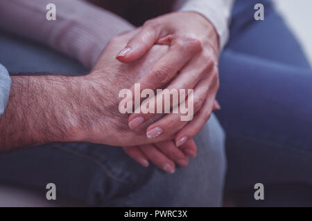 Close up of lovely couple holding by hands - Stock Photo