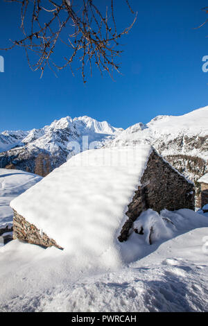 Hut covered with snow with Monte Disgrazia on background, Alpe dell'Oro, Valmalenco, Valtellina, Lombardy, Italy - Stock Photo
