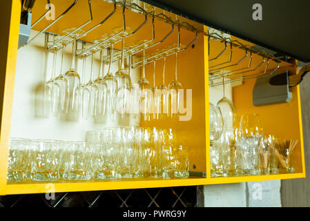 glass and crystal glasses suspended on fasteners in the wall - Stock Photo