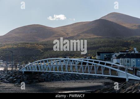 Footbridge over River Shimna connecting promenades with view to Mourne Mountains including Slieve Donard. Newcastle, County Down, N.Ireland. - Stock Photo