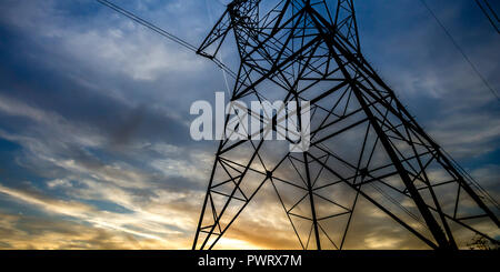 Tall steel tower supporting electrical wires. View of a tall steel tower under dark cloudy sky. The tower holds up electric cables used for electrical - Stock Photo
