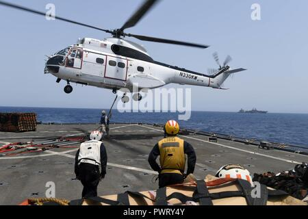 U.S. 5TH FLEET AREA OF OPERATIONS (June 22, 2017) Marines assigned to combat cargo aboard the amphibious dock landing ship USS Carter Hall (LSD 50) attach retrograde to an SA-330J Puma helicopter during an underway replenishment with the dry cargo and ammunition ship USNS Washington Chambers (T-AKE 11). Carter Hall, part of the Bataan Amphibious Ready Group, is deployed to the U.S. 5th Fleet area of operations in support of maritime security operations to reassure allies and partners, and preserve the freedom of navigation and the free flow of commerce in the region. ( - Stock Photo