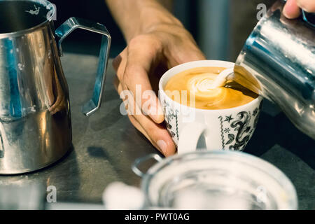 Close-up of a male barista hands pouring hot foam milk on a cup to make latte art cappuccino. - Stock Photo