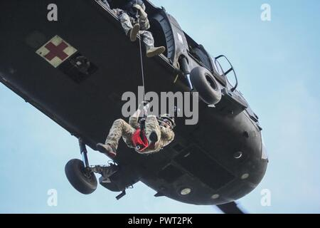 U.S. Air National Guard Senior Airman Michael Curley descends from a UH-60 Black Hawk helicopter during joint training for New Jersey Task Force One at Joint Base McGuire-Dix-Lakehurst, N.J., June 28, 2017. The primary mission of New Jersey Task Force One is to provide advanced technical search and rescue capabilities to victims trapped or entombed in structurally collapsed buildings. Task Force One is made up of New Jersey National Guard Soldiers and Airmen, as well as civilians. - Stock Photo