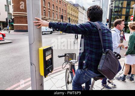 London England United Kingdom Great Britain Southwark street pedestrian crossing crosswalk signal activation box cyclist bicycle man rider waiting tra - Stock Photo