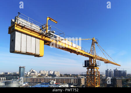 High building construction site. Big industrial tower crane with blue sky amd cityscape on background. Concrete plates weight balance. Counterweight. Aerial drone view. Metropolis city development - Stock Photo