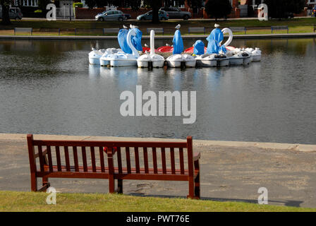 Pedalos in the shape of swans, Canoe Lake, Southsea, Porstmouth, Hampshire, England, partly covered as out of season. Empty seat in foreground. - Stock Photo