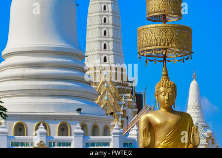 A large Buddha statue stands in front of white chedis at Wat Pichaiyat in Bangkok, Thailand, its hands in the Abhaya or Freedom from Fear gesture
