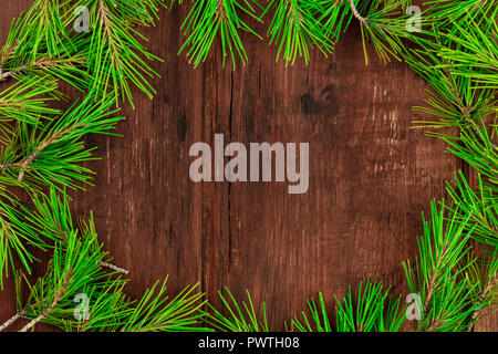 A Christmas composition with fir tree branches on a dark wooden background with copy space, shot from the top - Stock Photo