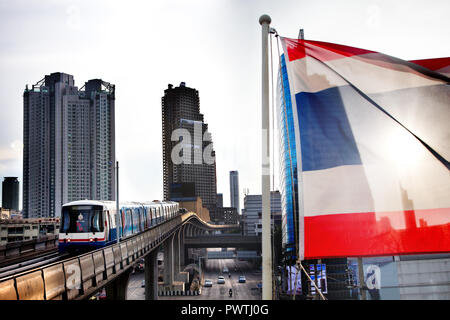 Skyscraper and Skytrain in the center of the city of Bangkok. Flag of Thailand - Stock Photo