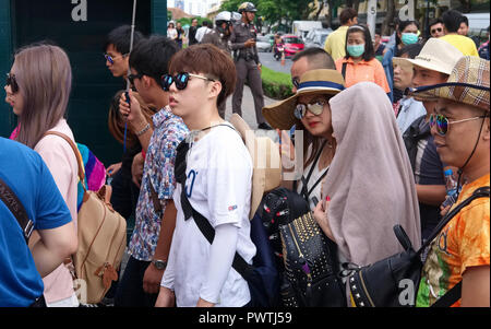 A group of Chinese tourists on a package tour entering Wat Phra Kaew (or Wat Phra Gaew, Wat Phra Keo) in Bangkok, Thailand - Stock Photo