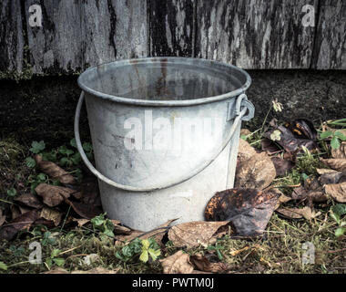 Old fashioned bucket sitting on the ground by an old wooden building with fall leaves. - Stock Photo
