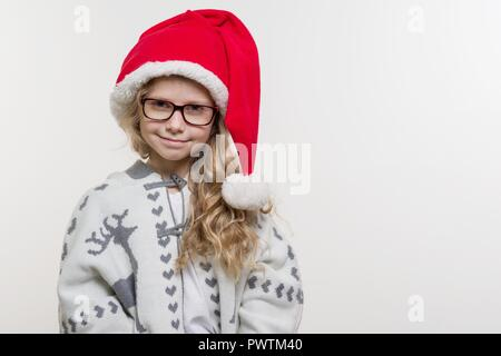 Winter holidays - an open portrait of funny girl of 7 years in a Santa Claus hat, glasses, knitted sweater with a traditional pattern - deer, on light - Stock Photo