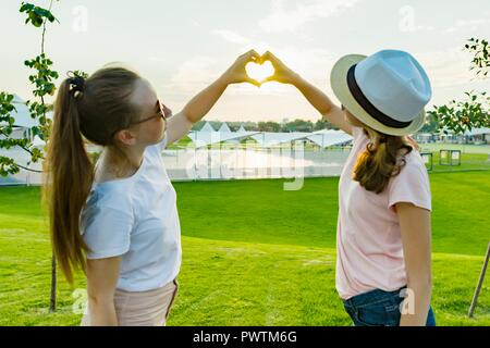 The friendship of two teenage girls, best girlfriends have fun in nature, on the green lawn of recreation park and entertainment, show hands on heart
