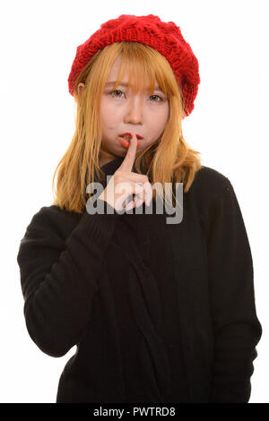 Young cute Asian woman with finger on lips - Stock Photo