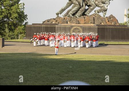 The U.S. Marine Drum and Bugle Corps perform during a sunset parade at the Marine Corps War Memorial, Arlington, Va., June 20, 2017. Sunset parades are held as a means of honoring senior officials, distinguished citizens and supporters of the Marine Corps. - Stock Photo