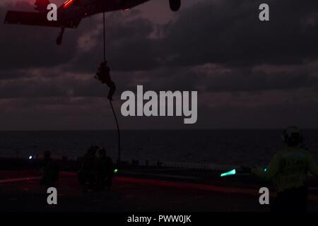 A Marine with the 31st Marine Expeditionary Unit's Force Reconnaissance Platoon rappels from a Navy MH-60S Seahawk helicopter toward the flight deck during low-light fast rope training aboard the USS Bonhomme Richard (LHD 6), underway in the Pacific Ocean, June 25, 2017. The FRP Marines train regularly for quick, tactical raids of targets on both land and sea. Fast roping allows Marines to enter inaccessible locations via rope from a hovering aircraft. The 31st MEU partners with the Navy's Amphibious Squadron 11 to form the amphibious component of the Bonhomme Richard Expeditionary Strike Grou - Stock Photo