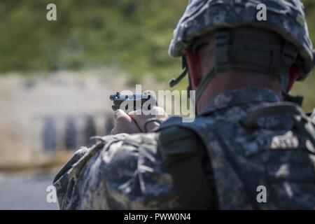A U.S. Army Soldier, assigned to Multinational Battle Group-East, participates in a multinational pistol competition on Camp Bondsteel, Kosovo, June 21. The competitors fired two 5-round magazines from a 9mm pistol at four different distances; standing, kneeling, and prone. - Stock Photo