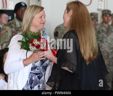 Outgoing U.S. Army Alaska Task Force Commander Col. Blake Alexander's wife, Lori, is presented flowers by USARAK Commander Maj. Gen. Bryan Owens' wife, Jen, at the UATF change of command June 29 at Fort Wainwright, Alaska. Lori Alexander served as an Armed Services YMCA staff member throughout her time in Alaska. - Stock Photo
