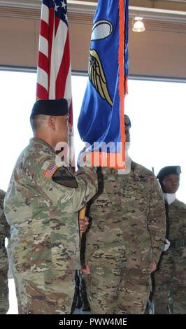 """Incoming U.S. Army Alaska Aviation Task Force Commander Col. Glen Heape holds the task force colors for the first time after accepting them and the leadership of the """"Arctic Falcons"""" from USARAK Commander Maj. Gen. Bryan Owens during the UATF change of command June 29 at Fort Wainwright, Alaska. - Stock Photo"""