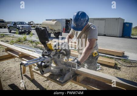 U.S. Air Force Senior Airman Richard Green, an Airman with the 128th Air Refueling Wing Civil Engineer Squadron, Wisconsin Air National Guard, operates a miter saw to make cuts to siding June 22, 2017, at the Crow innovative readiness training construction site. The Crow IRT is a deployment for training opportunity that provides training and readiness for military personnel while addressing public service needs. - Stock Photo