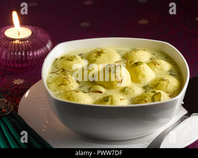 RASMALAI, AN INDIAN DESSERT MADE FROM COTTAGE CHEESE SOAKED IN SWEET SAFFRON MILK AND GARNISHED WITH PISTACHIO - Stock Photo