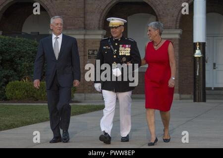 From left, Secretary James N. Mattis, Department ofDefense, Commandant of the Marine Corps Gen. Robert B. Neller, and D'Arcy Neller walk down center walk during an evening parade at Marine Barracks Washington, Washington, D.C., June 30, 2017. Neller hosted the parade and Mattis was the guest of honor. - Stock Photo