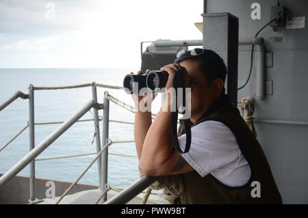 NOUMEA, New Caledonia (July 03, 2017) Sison Emerson, Able-Bodied Watchstander onboard USNS Sacagawea (T-AKE 2), stands watch off shore Noumea, New Caledonia in support of Koa Moana 17, July 3. Koa Moana 17 is designed to improve theater security, and conduct law enforcement and infantry training in the Pacific region in order to enhance interoperability with partner nations. ( - Stock Photo