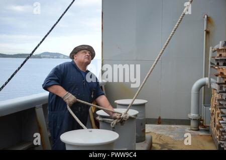 NOUMEA, New Caledonia (July 03, 2017) Robert Moore, Able-Bodied Seaman (maintenance) onboard USNS Sacagawea (T-AKE 2), assists in lift operations off shore Noumea, New Caledonia in support of Koa Moana 17, July 3. Koa Moana 17 is designed to improve theater security, and conduct law enforcement and infantry training in the Pacific region in order to enhance interoperability with partner nations. ( - Stock Photo