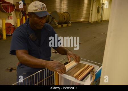 NOUMEA, New Caledonia (July 03, 2017) Joseph Celestine, Able-Bodied Seaman (maintenance) onboard USNS Sacagawea (T-AKE 2), files documents off shore Noumea, New Caledonia in support of Koa Moana 17, July 3. Koa Moana 17 is designed to improve theater security, and conduct law enforcement and infantry training in the Pacific region in order to enhance interoperability with partner nations. ( - Stock Photo
