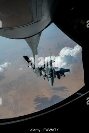 A French air force Rafale receives fuel from a U.S. KC-135 Stratotanker in support of Operation Inherent Resolve, July 1, 2017. The Rafale is a twin-engine fighter intended to perform air supremacy, interdiction, aerial reconnaissance, ground support, in-depth strike and anti-ship strike missions. - Stock Photo