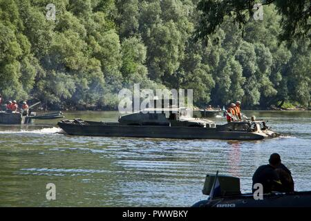 Engineers assigned to 837th Brigade Engineer Battalion, U.S. Army National Guard from Wooster, Ohio and 37th Engineer Regiment, Hungarian Defense Force ferry a Humvee in a PTS Amphibious Cargo Vehicle across the Mosoni-Duna River in Gyor, Hungary during exercise Szentes Axe 17 July 5, 2017. The Hungarian national exercise takes place June 26-July 7 to enable Saber Guardian 17 by conducting tactical bridging and water crossing operations for 2CR freedom of movement from home station into Hungary and many joint operations area locations. - Stock Photo