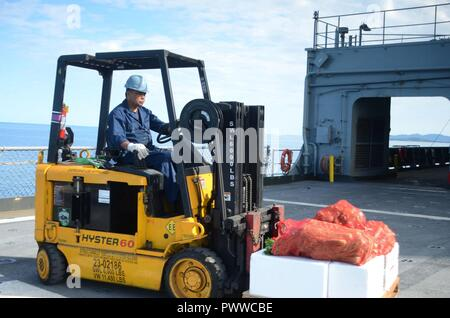 NOUMEA, New Caledonia (July 06, 2017) Nito Catunao, Boatswains Mate onboard USNS Sacagawea (T-AKE 2), operates a forklift during stores onload off shore Noumea, New Caledonia in support of Koa Moana 17, July 6. Koa Moana 17 is designed to improve theater security, and conduct law enforcement and infantry training in the Pacific region in order to enhance interoperability with partner nations. ( - Stock Photo