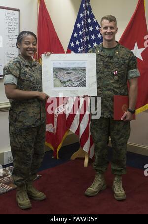 U.S. Marine Corps Maj. Jeremy S. Nelson, aide de camp, Installations and Logistics (I&L), left, poses for a photo with Sgt. Brittane M. Woodard, administrative chief, I&L, at the Pentagon, Arlington, Virginia, June 28, 2017. Nelson was awarded the Meritorious Service Medal due to his outstanding meritorious service from June 2014 to June 2017. - Stock Photo