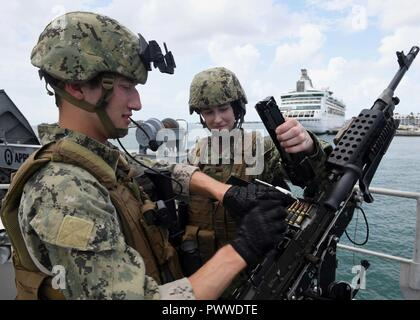 KEY WEST, Fla. (July 6, 2017) Master-at-Arms 2nd Class Timothy Faulkner, left, and Master-at-Arms 2nd Class Laura Kelley, both assigned to Coastal Riverine Group One detachment Guam, load a M240 machine gun aboard USNS Spearhead (T-EPF 1).  SPS-EPF 17 is a U.S. Navy deployment, executed by U.S. Naval Forces Southern Command/U.S. 4th Fleet, focused on subject matter expert exchanges with partner nation militaries and security forces in Central and South America.  ( - Stock Photo