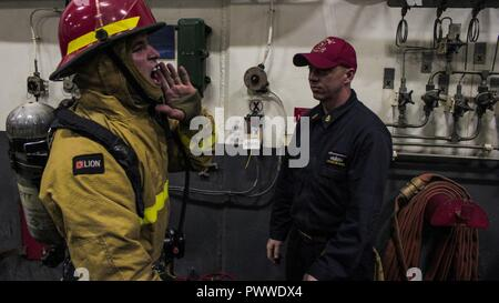 SOUTH PACIFIC (July 4, 2017) Chief Hull Technician (SW/AW) Chance Mays, right, from Fayetteville, North Carolina, observes a Sailor simulating proper procedures and calls for activating an aqueous film forming foam station during a general quarters drill in the hangar bay aboard the Navy's forward-deployed aircraft carrier, USS Ronald Reagan (CVN 76). Ronald Reagan, the flagship of Carrier Strike Group 5, provides a combat-ready force that protects and defends the collective maritime interests of its allies and partners in the Indo-Asia-Pacific region. ( - Stock Photo
