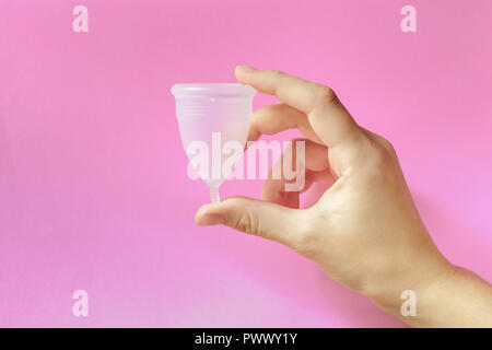 Close up of woman hand holding menstrual cup over pink background. Women health concept, zero waste alternatives - Stock Photo