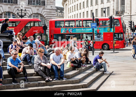 London England United Kingdom Great Britain West End Piccadilly Circus St. James's Shaftesbury Memorial Fountain steps man woman boy sitting red doubl - Stock Photo