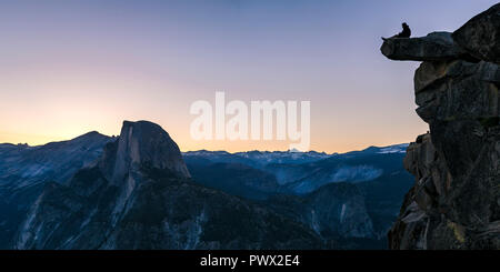 Man on a cliff with view of rock mountain below - Stock Photo