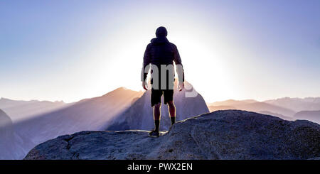 Man on a cliff with view of sun and mountains - Stock Photo