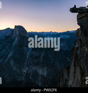 Man sitting at the edge of a cliff in Yosemite - Stock Photo