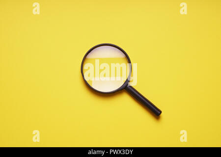 magnifying glass magnifier loupe search symbol on yellow background with copy space - Stock Photo