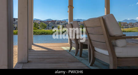 Patio overlooking lake and homes on a sunny day - Stock Photo