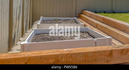 Seed box filled with soil inside a sunny backyard - Stock Photo