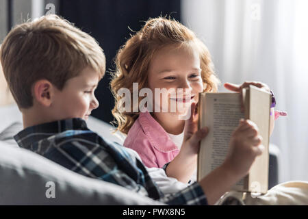 little boy reading book while his sister interrupting him - Stock Photo
