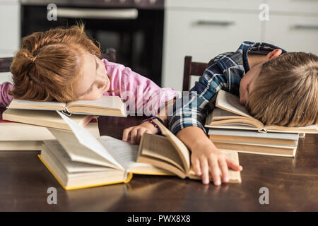 exhausted little scholars sleeping on book while doing homework Stock Photo